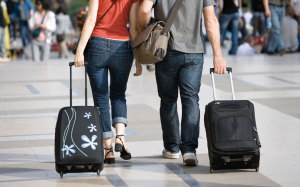 Couple walking outdoors with rolling luggage