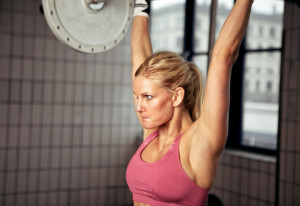 Concentrated Woman Lifting Weight